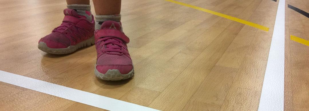 Kid standing on a new gymnasium floor