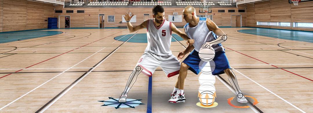 Two men playing basketball in gymnasium
